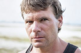 stock photo of predator  - Closeup portrait of rugged Caucasian man with stern bold facial expression distinct features and intense predator eyes in undefined outdoor environment - JPG