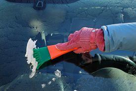 stock photo of scrape  - Winter scene human hand in glove scraping ice from windshield of car - JPG