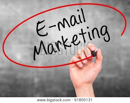 Man Hand writing E-mail Marketing with marker on transparent wipe board.