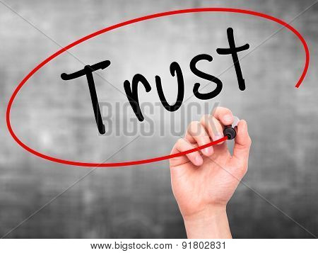 Man Hand writing Trust black marker on visual screen.
