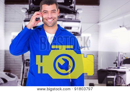 Portrait of smiling male mechanic using mobile phone against auto repair shop