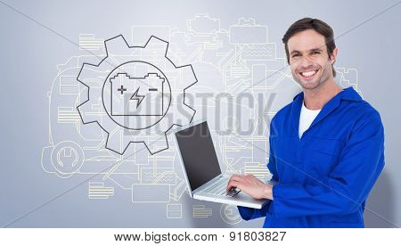 Handsome mechanic using laptop over white background against grey vignette