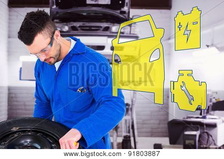 Mechanic working on tire against auto repair shop
