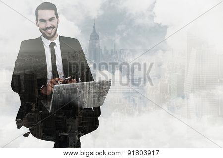 Happy businessman with laptop using smartphone against new york