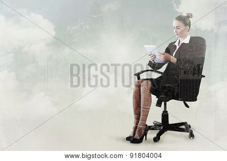 Businesswoman sitting on swivel chair with tablet against new york skyline