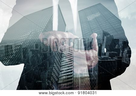 Businessman sending a text message against low angle view of skyscrapers