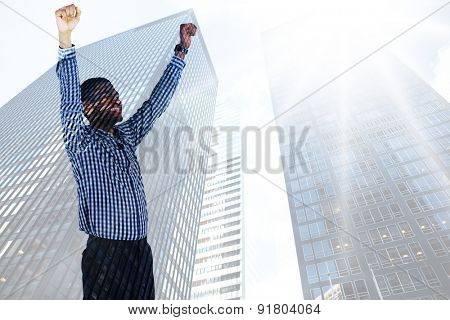 Excited businessman cheering against low angle view of skyscrapers