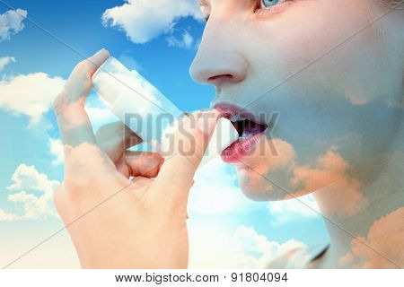 Blonde woman taking her inhaler against blue sky