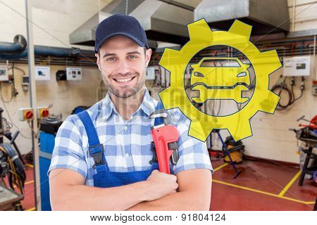 Confident young male repairman holding adjustable spanner against workshop