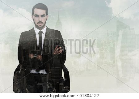 Serious businessman sitting with arms crossed against new york