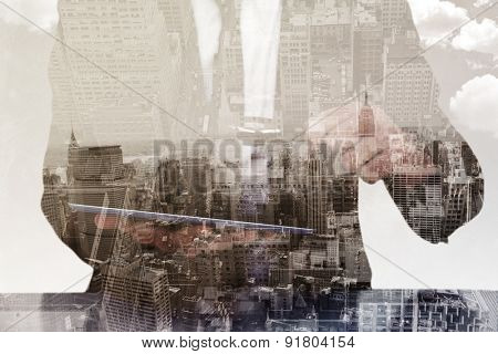 Businessman looking at his tablet through magnifying glass against new york skyline