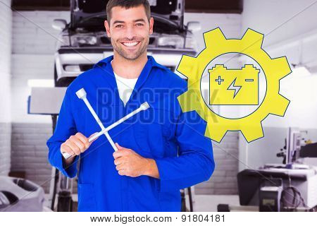 Smiling male mechanic holding lug wrench against auto repair shop