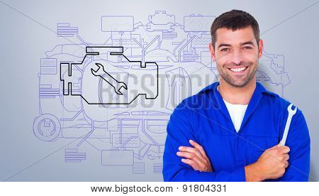 Smiling male mechanic holding spanner against grey vignette