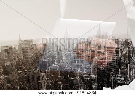 Businessman scrolling on his digital tablet against new york skyline