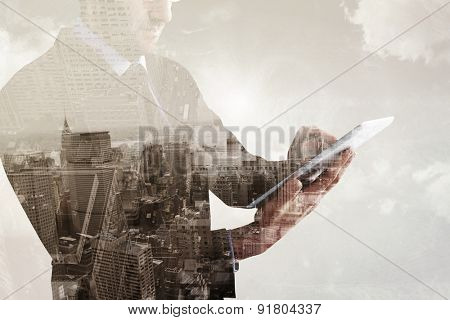 Mid section of a businessman using digital tablet against new york skyline