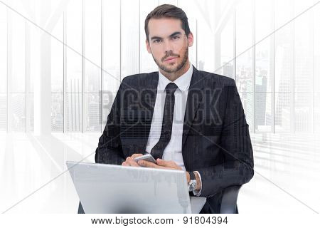 Cheerful businessman with laptop using smartphone against room with large window looking on city