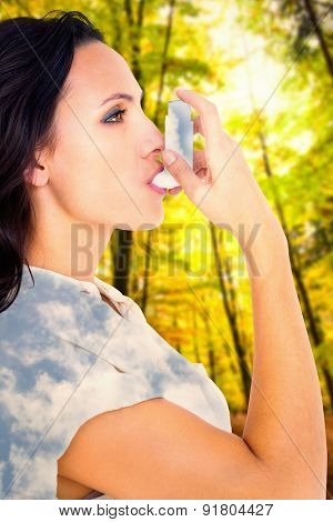 Asthmatic brunette using her inhaler against bright blue sky with clouds