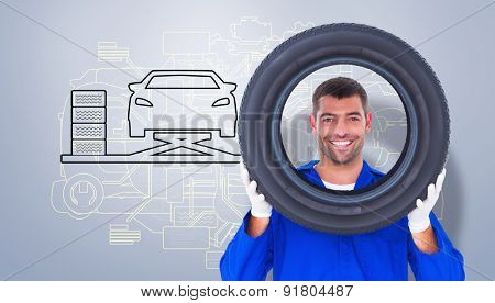 Happy mechanic looking through tire against grey vignette