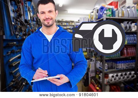 Male mechanic writing on clipboard against full store room
