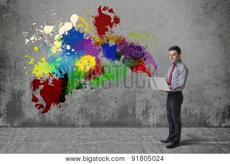 creative business man using laptop against grunge background
