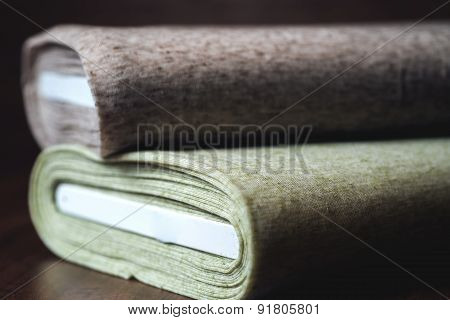 Rolls of fabric on wooden background