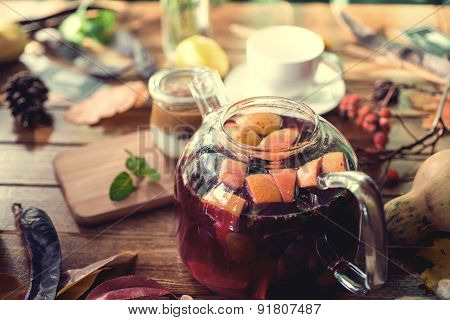 Delicious dessert with banana and caramel, fruit red tea on wooden background. Autumn concept