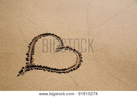 Heart drawing on dry sand