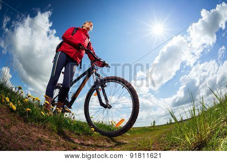 Young lady standing with bicycle on a green summer meadow at sunny day