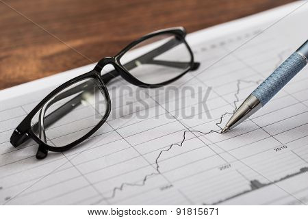 Pen And Eyeglasses On Graph Paper