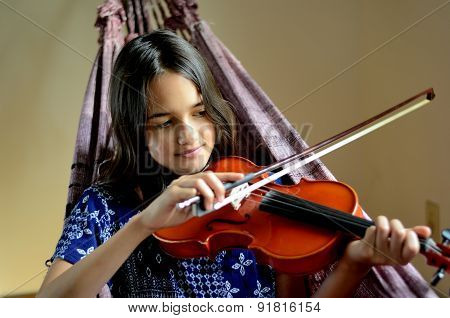 Little girl in a hammock playing violin