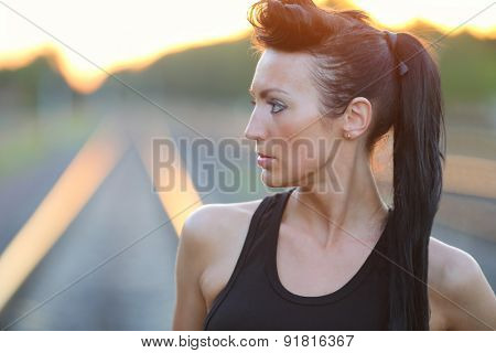 Portrait of a beautiful young girl in a black shirt on a railway track at sunset