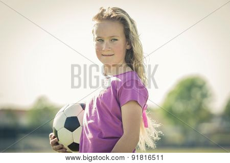 Young female soccer player posing with ball