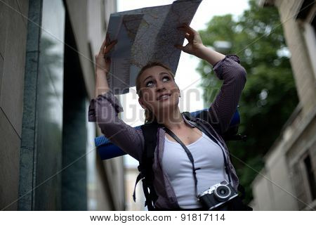 Young female backpacker trying to protect herself from rain