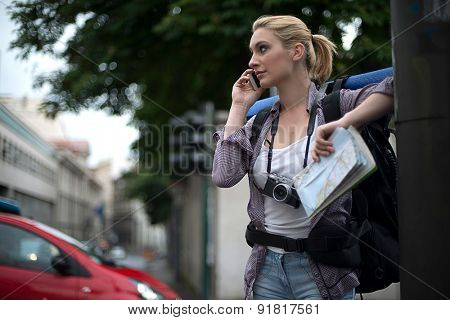 Young female backpacker using mobile phone