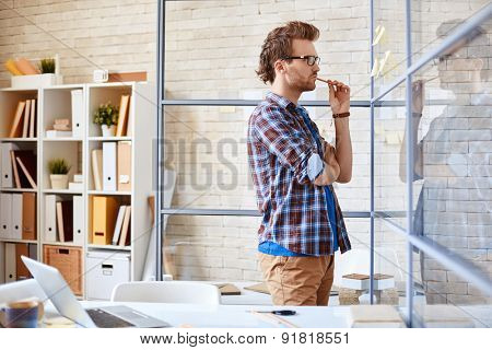 Pensive businessman reading reminders in office