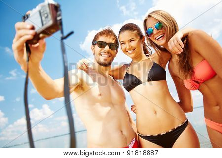 Happy friends taking photos on the beach