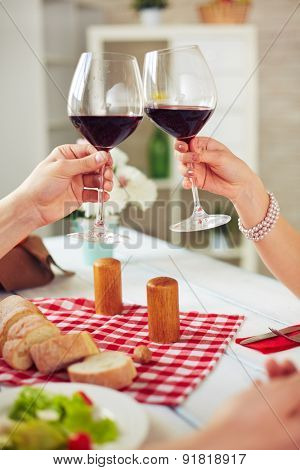 Hands of couple with glasses with red wine during toast