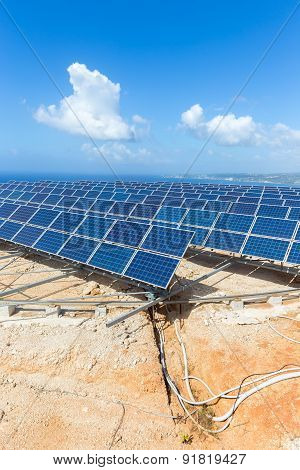 Rows of solar panels near sea with blue sky