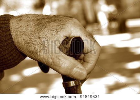 closeup of the hand of an old caucasian man with a walking stick, in sepia toning