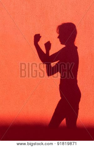 Silhouette of woman showing fists on red wall
