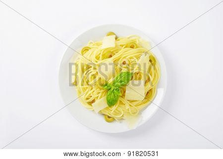 heap of boiled spaghetti with slices of parmesan cheese, green olives and fresh basil on white plate
