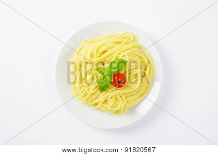 heap of boiled spaghetti, basil and cherry tomato on white plate