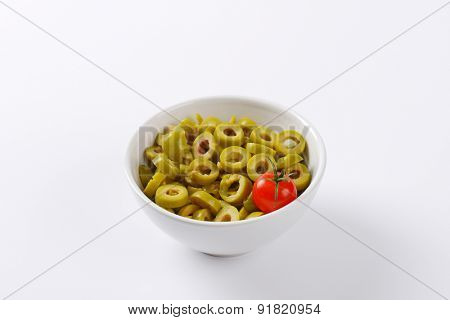 bowl of sliced green olives on white background
