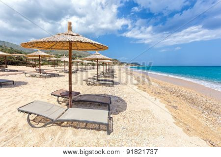 Beach umbrellas in rows on sandy beach with sea