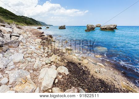 Landscape with boulders and rocks on coast with blue sea