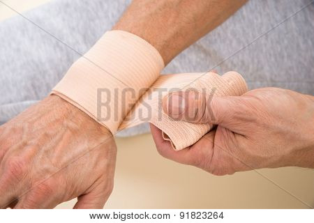 Man Tying Bandage To His Wrist