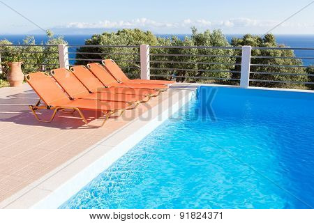 Row of orange loungers near blue swimming pool