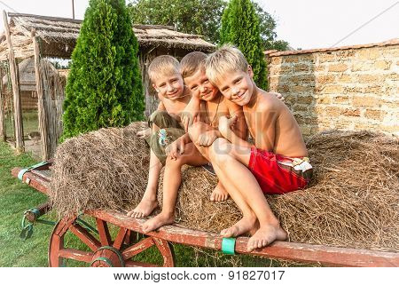 boys sitting on a hay bale