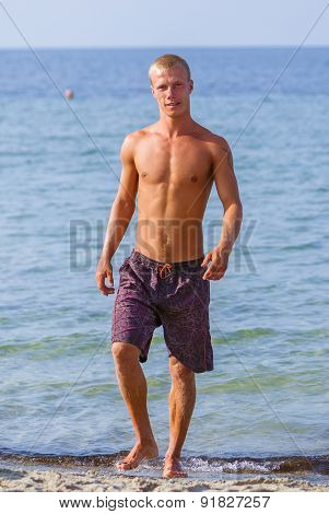 healthy young man walking in ocean water