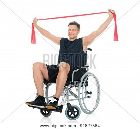 Disabled Man On Wheelchair Exercising With Resistance Band